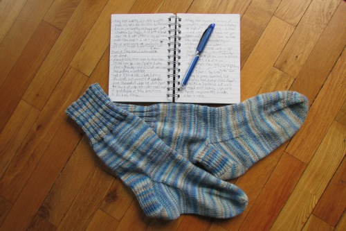 Please enjoy a picture of one of my notebooks, with bonus hand-knit socks.